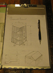 A rough sketch of a free standing rotating bookcase, on top is an angled reading surface hinged to contain a secret compartment