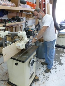 Here's the Big Man feeding the cedar blanks into the shaper, near-side is a power feeder.  It's like a tiny tank that moves the blank through the shaper.  Gorgeous.