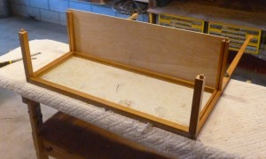 The front and back of the case were glued up first.  Here the floor is being fitted into kerfs in the bottom case frame.