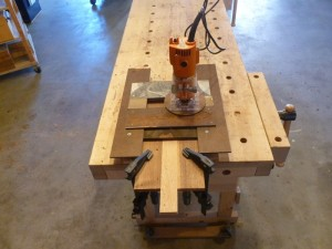 Here, just before Lift-off, the trim router sits atop the jig all clamped securely (we trust) to the case mod front.